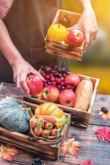 Farmer with fresh fruit on hands. fall harvest cornucopia. autumn season with fruit and vegetable. thanksgiving day concept.