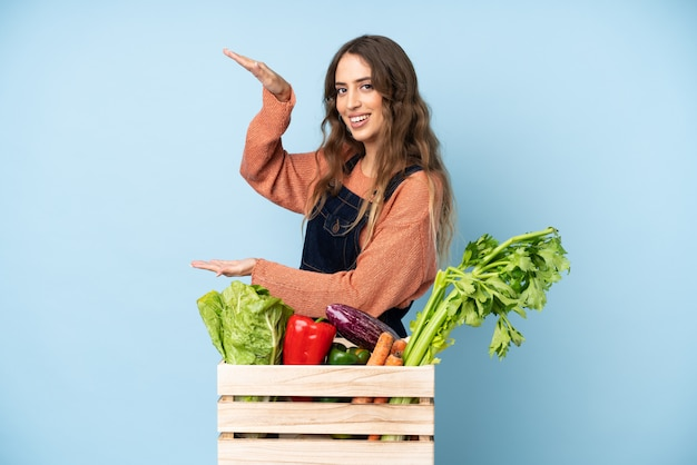 Farmer with freshly picked vegetables in a box holding copyspace to insert an ad