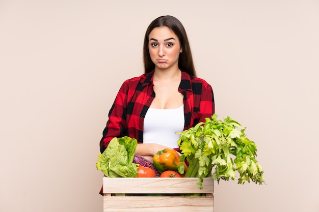 Farmer with freshly picked vegetables in a box isolated on beige wall sad