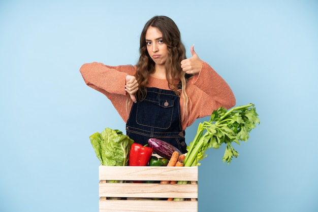 Farmer with freshly picked vegetables in a box making good-bad sign. undecided between yes or not