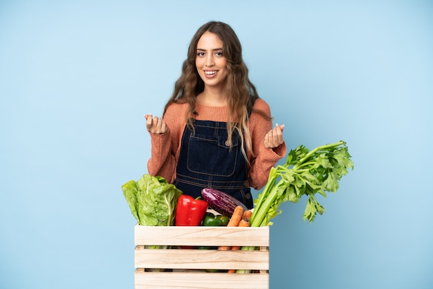 Farmer with freshly picked vegetables in a box making money gesture