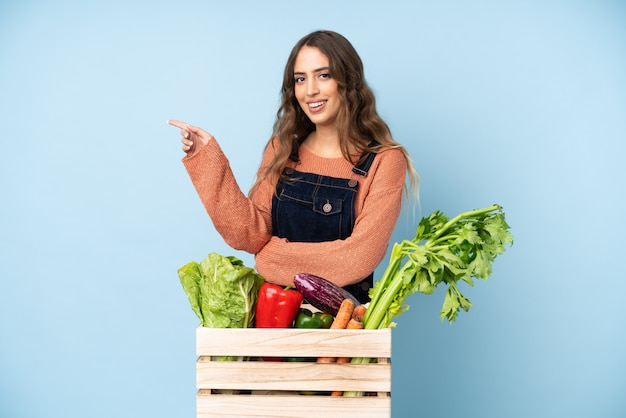 Farmer with freshly picked vegetables in a box pointing finger to the side