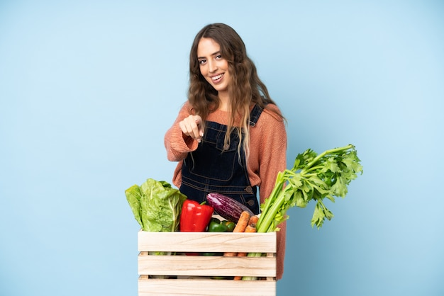 Farmer with freshly picked vegetables in a box points finger at you with a confident expression