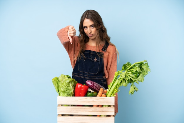 Farmer with freshly picked vegetables in a box showing thumb down with negative expression