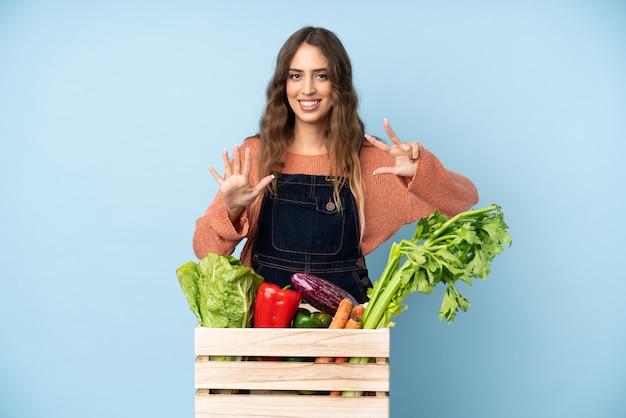 指で8を数えるボックスで摘みたての野菜を持つ農家