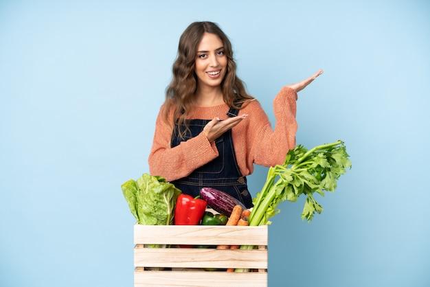 来るように誘うために横に手を伸ばす箱に摘みたての野菜を持つ農家