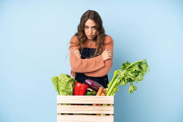 Фермер со свежесобранными овощами в коробке заморозки