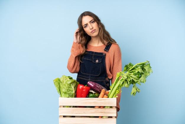 疑わしい箱に摘みたての野菜を持つ農家