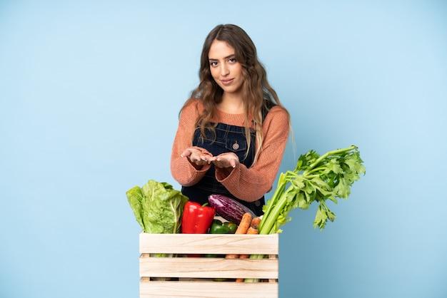 手のひらにcopyspaceの想像上の広告を挿入するためのボックスに摘みたての野菜を持つ農家