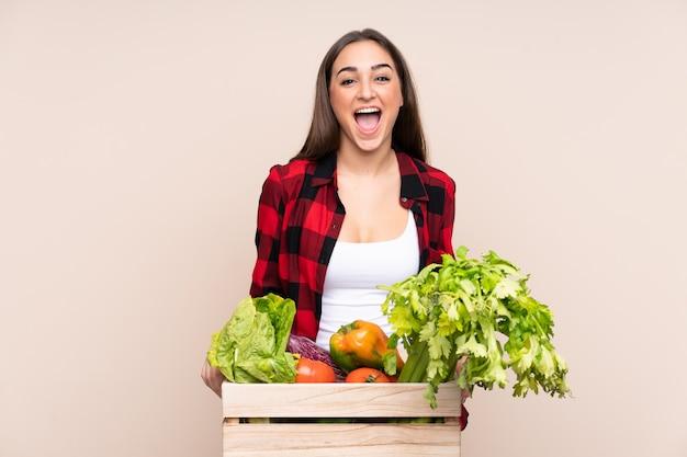 Фермер со свежесобранными овощами в коробке на бежевом фоне с удивленным выражением лица
