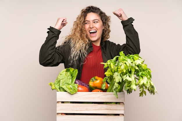 Фермер со свежесобранными овощами в коробке на бежевом фоне празднует победу