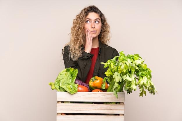 Фермер со свежесобранными овощами в коробке изолирован на бежевом, думая об идее