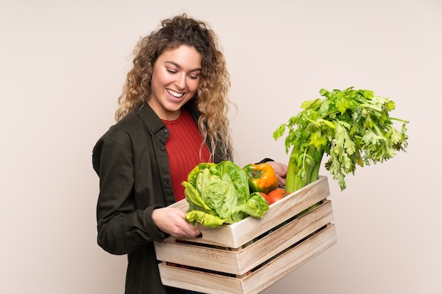 ベージュで隔離された箱に採れたての野菜を持っている農家