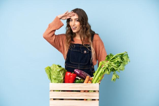 摘みたての野菜を手に持って遠くを見ている農家の農家