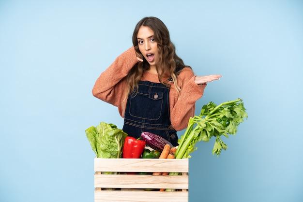 Фермер со свежесобранными овощами в коробке делает жест телефона и сомневается