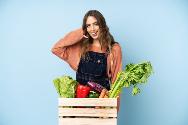 Фермер со свежесобранными овощами в коробке, делая жест телефона