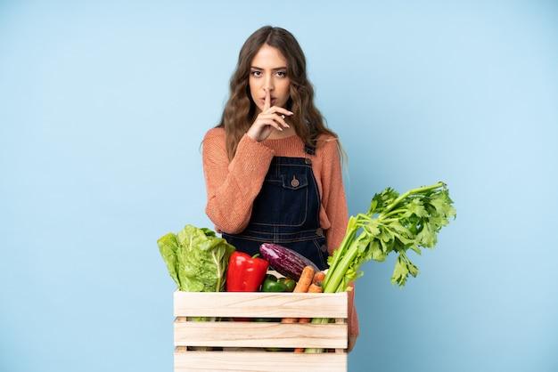 口に指を入れて沈黙ジェスチャーの兆候を示すボックスで摘みたての野菜を持つ農家