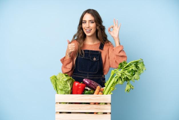 Фермер со свежесобранными овощами в коробке, показывающей знак ок и большой палец вверх