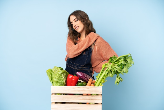 努力したために肩の痛みに苦しんでいる箱に摘みたての野菜を持つ農家