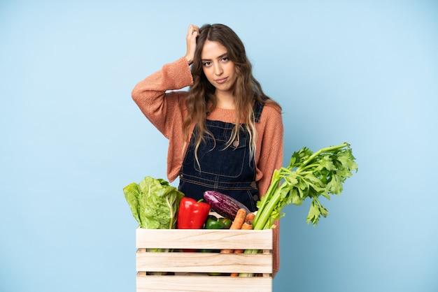 欲求不満の表現と理解していない箱に摘みたての野菜を持つ農家