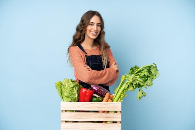 腕を組んで、楽しみにしてボックスで摘みたての野菜を持つ農家