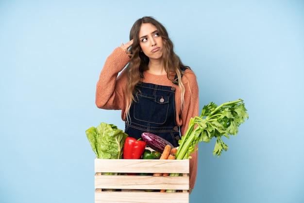 自殺ジェスチャーを作るのに問題がある箱に摘みたての野菜を持つ農家