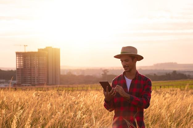 Фермер в шляпе и мобильном планшете анализирует плантацию на закате.
