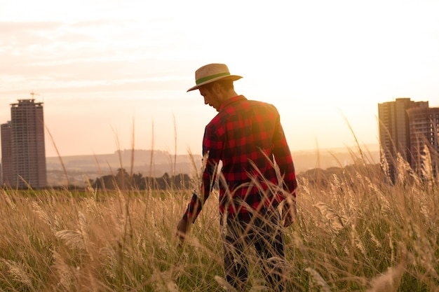 Фермер в шляпе на ферме на закате.