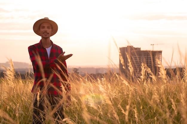 Фермер в шляпе на ферме, указывая на закат.
