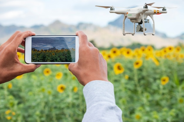 Farmer with smart phone on field with drone flying above farmland