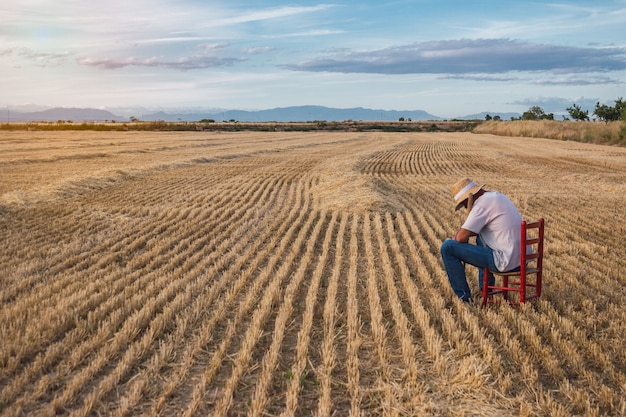 Фермер в соломенной шляпе и мотыге сидит на красном стуле посреди поля. концепция сельского хозяйства.