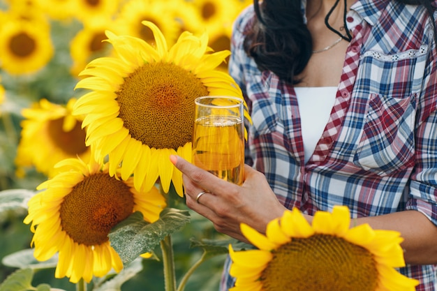 Farmer with sunflower oil at sunflowers field