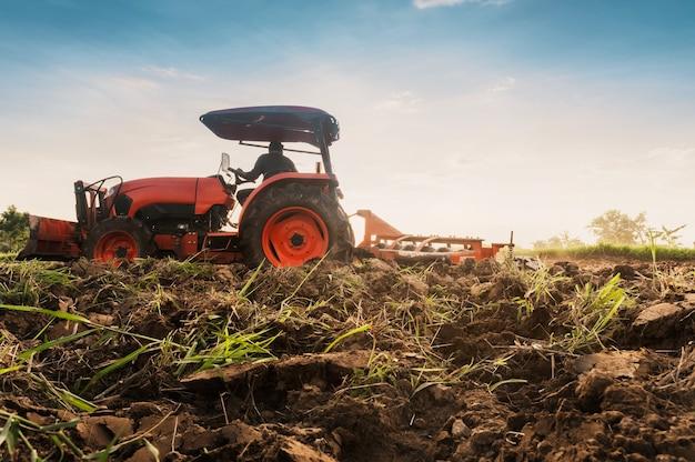 トラクターを持っている農民は農作物を栽培するために土地を準備します。