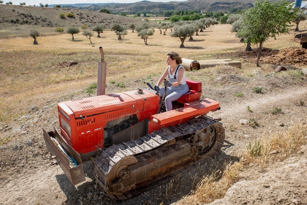 Farmer woman driving a tractor in the field