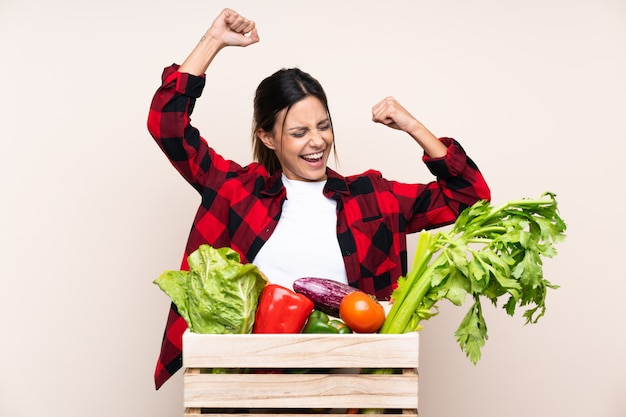 Farmer woman holding fresh vegetables in a wooden basket celebrating a victory