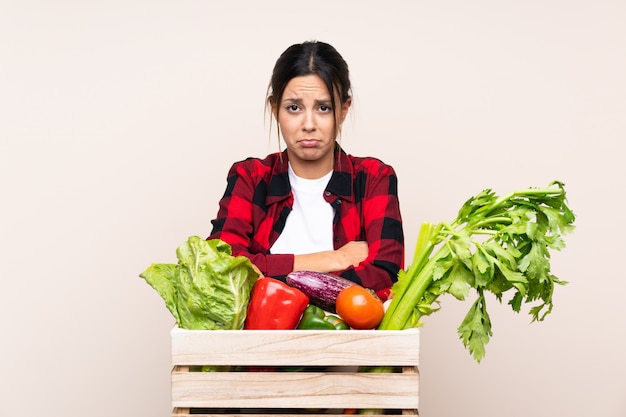 Farmer woman holding fresh vegetables in a wooden basket sad
