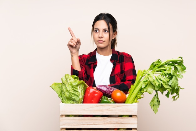 Farmer woman holding fresh vegetables in a wooden basket touching on transparent screen