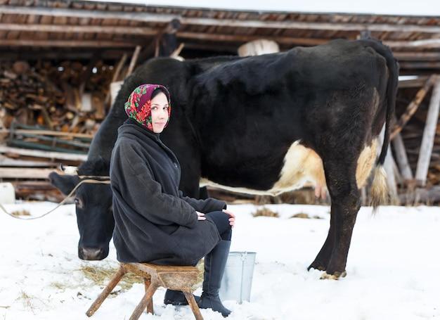 牛を搾乳する伝統的なロシアのドレスを着た農家の女性