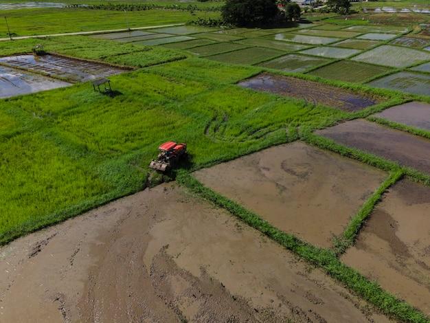 Фермер, работающий на рисовой плантации с помощью трактора-культиватора. вид с воздуха фермер готовит посадку риса. поля с сельскохозяйственных культур в сельской местности лампанг, таиланд.