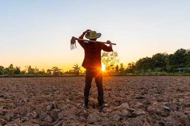 屋外の夕日にフィールドで働く農夫