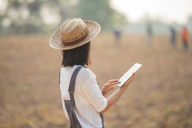 현대 농업에서 태블릿을 사용 하여 필드에서 작업하는 농부.