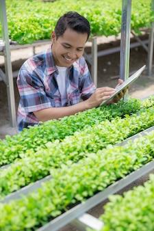 Фермер работает с планшетом в ферме