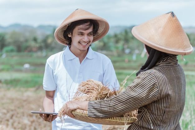 농부들은 밭에서 태블릿 pc를 사용하여 남성 농부들에게 짠 대나무 쟁반에 쌀 수확량을 보여줄 때 행복합니다.