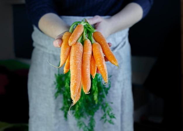 新鮮なニンジンを持っている農民。新鮮な束の収穫を保持している女性の手。健康的な有機食品、野菜、農業、クローズアップ。高品質の写真