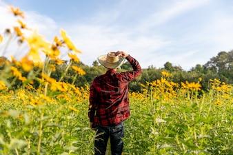 農家は晴れた夏の花の農場を調べます。