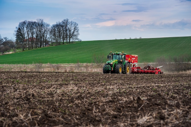 農民は、耕作地でpottinger terrasemc8シーダーを備えたjohndeere8370rトラクターを使用して肥料を播種します。