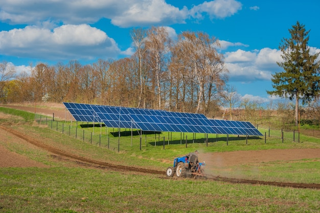 Farmers tractor plowing, spring work on field and solar panel with cloudly sky