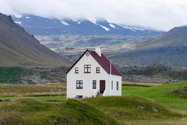 曇り空と素晴らしい景色を望むアイスランドの丘の上の農家