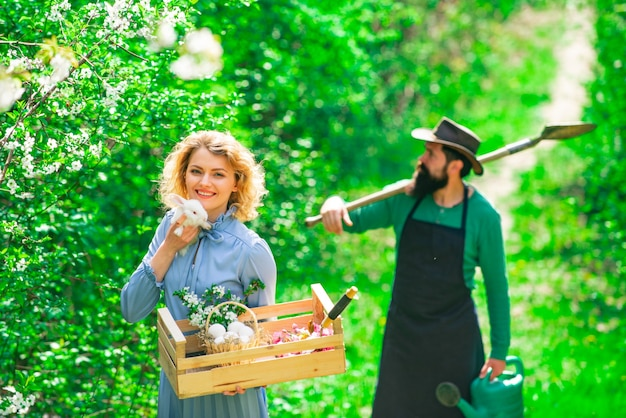 Farming gardening and people concept couple of farmers seedling sprouts in the garden country life