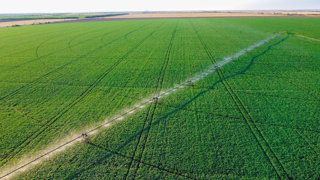 Farming irrigation sprinklers system on cultivated agricultural landscape field aerial view